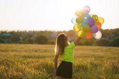 Young girl with big bunch of colorful balloons royalty free stock photo