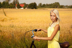 Young girl with a bike in the countryside. Royalty Free Stock Photo