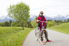 Young girl with the bike in the mountains Royalty Free Stock Image