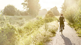 Young girl on bike. Photo taken outdoor in summer royalty free stock image