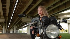Young girl biker in leather jacket sitting on parking motorcycle on urban background. Rock girl posing on motorbike stock video