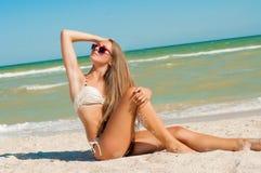 Young girl in a bikini on the beach Stock Photos
