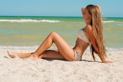 Young girl in a bikini on the beach Stock Images