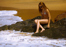 Young girl in bikini with beutiful body and sunglasses near red stones on the beach Royalty Free Stock Images