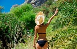 Girl in bikini and hat have rest in palm forest. Young girl in bikini and hat have rest in palm forest of Preveli, Crete, Greece stock photo