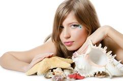The young girl in bikini lays with seashells Royalty Free Stock Image