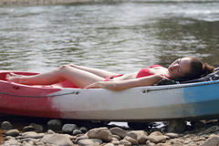 A young girl in bikini lying on the boat and sunbathing near the river, enjoying holidays in Laos Stock Image