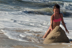 Young girl in bikini playing with Sands at Sea Shore Stock Images