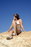 Young girl in bikini sitting on the rocks Stock Photography