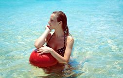 Young girl in bikini swimming on a tropical beach Royalty Free Stock Images