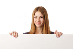 Young Girl with Billboard. Smiling young girl with blank white board over white background Royalty Free Stock Photos