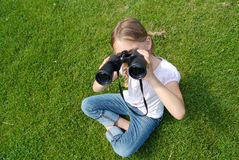 Young girl with binoculars looking up. A young girl with a pair of binoculars is looking up royalty free stock photography