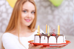 Young girl with a birthday cake and cone cap Royalty Free Stock Photos