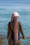 Young girl in a black bathing suit and cap with long pink pigtai. African young girl in a black bathing suit and cap with long pink pigtails posing in the Stock Image