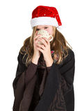 Young girl with black cape and red winter cap holding cup. Isolated on white background Royalty Free Stock Photography