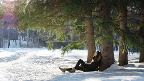 Young girl in black coat sitting on the thawed patch a tree in the snow in a fabulous wild forest. Stock Images