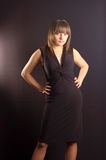 Young girl in a black dress. Against a background Royalty Free Stock Photography