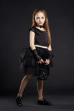 Young girl in a black dress with black bag on a black background. Girl is preparing for Halloween holiday. Young girl in a black dress with black bag on a black Stock Image