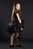Young girl in a black dress with black bag on a black background. Girl is preparing for Halloween holiday. Young girl in a black dress with black bag on a black Stock Images