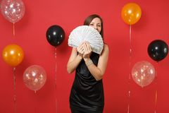 Young girl in black dress hiding, covering face with bundle lots of dollars, cash money in hand on bright red background. Air balloons. Women`s Day Happy New stock photo