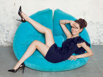 Young girl in a black dress lying on blue sofa. Royalty Free Stock Photo