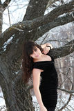 A young girl in a black dress. Near the tree Royalty Free Stock Photos
