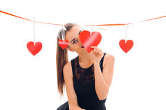 A young girl in a black dress with Red Ribbon stands near hearts royalty free stock image