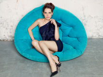 Young girl in a black dress sitting on blue sofa. Stock Images