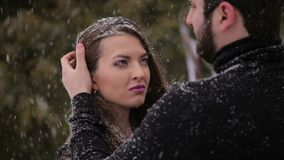 Bride in a black dress. Gothic wedding. Winter. Young girl in black dress standing under a heavy snowfall and shivers from the cold. Man gently stroking the stock footage