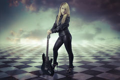Young girl with black electric guitar.gamero chess, pieces marbl Royalty Free Stock Images