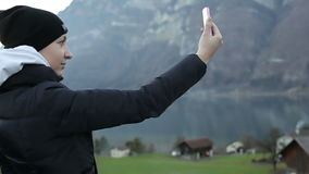 Young girl in a black hat and a winter jacket makes selfi against the backdrop of the Alps. stock video footage