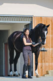 Young girl and black  horse Royalty Free Stock Image