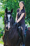 Young girl and black  horse Stock Photography