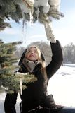 A young girl in a black jacket touches icicles Royalty Free Stock Photo