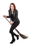 Young girl in black leather jacket riding wicked broom isolated Stock Image