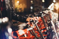 Young girl in black leather jacket using bike on background illumination glow bokeh light in night atmospheric city, hipster bikin. G and riding to work by stock photo