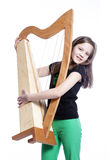 Young girl in black shirt carries harp in studio and smiles Royalty Free Stock Photo