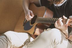 Young girl in black shirt playing guitar stock images