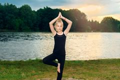 Young girl in black T-shirt and leggings sits on a stone in lotus pose near the lake stock photos