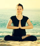Young girl in black T-shirt is sitting and sitting and doing yog. A on the beach near ocean Royalty Free Stock Photos