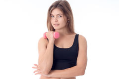 Young girl in black top looks forward and keeps the dumbbell is isolated on a white background. Young girl in black top looks forward and keeps the dumbbell is Royalty Free Stock Photos