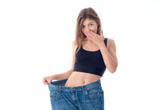 Young girl in black top stands in extensive denim pants and closes the mouth hand isolated on white background Stock Images