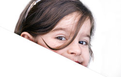 Young girl with a blank board. Smiling young girl peeking behind a blank white board Royalty Free Stock Images