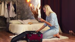 A young girl blogger sitting on her knees takes a video on her phone of the contents of a suitcase lying on the floor
