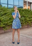 Young girl blonde in blue short dress eats pie Stock Photos
