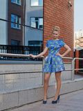 Young girl blonde in blue short dress. To utmost high-heeled Royalty Free Stock Image