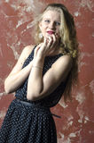 Young girl with blonde curly hair in a long dress with polka dots Stock Photography
