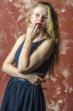 Young girl with blonde curly hair in a long dress with polka dots Stock Photo
