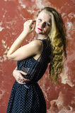 Young girl with blonde curly hair in a long dress with polka dots Royalty Free Stock Photo