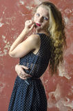 Young girl with blonde curly hair in a long dress with polka dots Royalty Free Stock Images